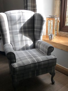 A completed traditional wing back chair completed ina woolen check